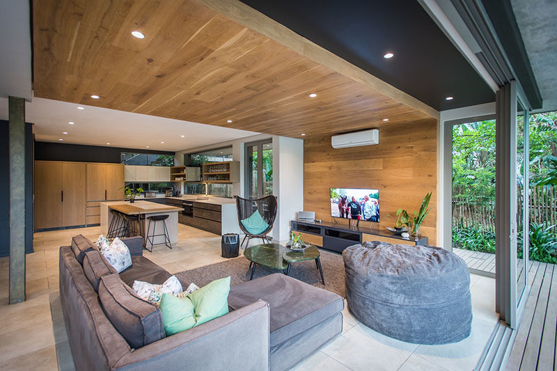 LIVING ROOM IDEAS - One of the most eye-catching design elements of this modern interior by Metropole Architects, was the inclusion of a wrap-around wood accent wall in the living room that travels from the wall up onto the ceiling. #LivingRoom #WoodAccentWall #WoodCeiling #InteriorDesign #AccentWall #LivingRoomIdeas