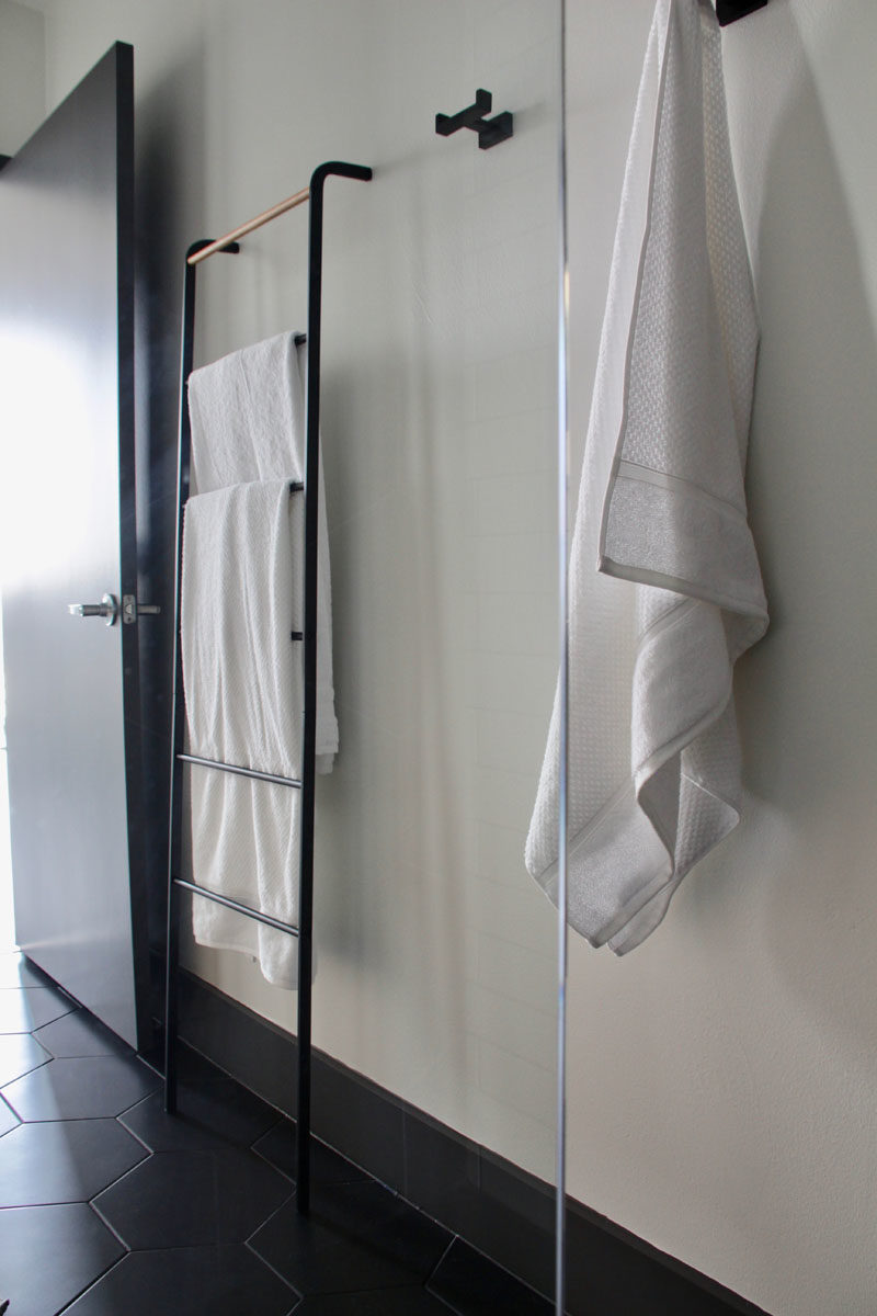 In this modern bathroom, black hooks and a towel rack create a space to hang towels and clothes. #BathroomDesign #BathroomHooks #TowelRack