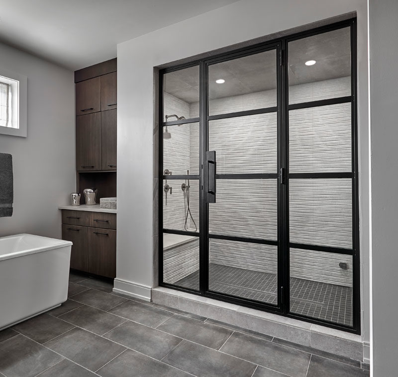 Shower Ideas - In this modern master bathroom, the walk-in shower is enclosed behind a blackened steel and glass door. Inside the shower, large format striated wall tile has been combined with a black mosaic shower floor tile for a modern industrial look. #ShowerIdeas #ModernShower #ShowerDesign