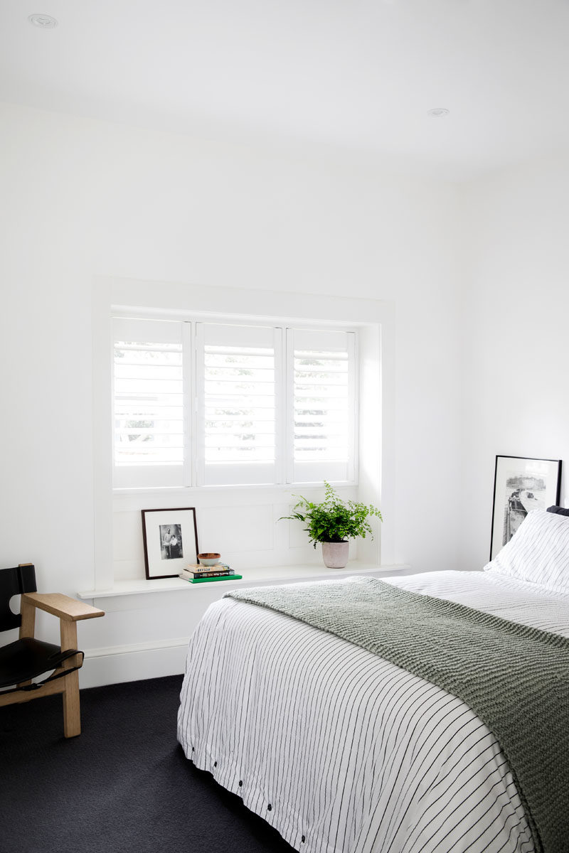 Bedroom Ideas - In this contemporary bedroom, dark carpet creates a soft touch underfoot, and contrasts the bright white walls. #BedroomIdeas #DarkCarpet #ContemporaryBedroom