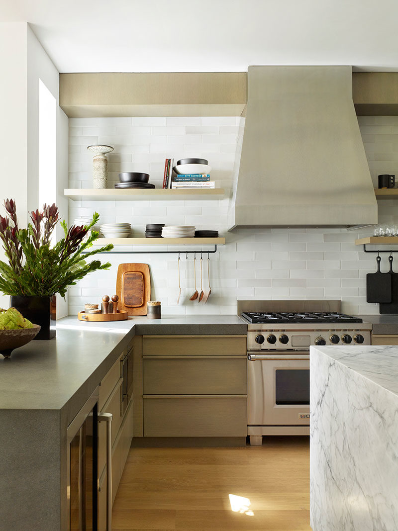Kitchen Ideas - In this contemporary kitchen, thick honed basalt has been used for the back counters, and handmade tiles from Heath Ceramics are showcased on the backsplash. Above the stone island is a custom architectural chandelier from the Thomas Hayes Gallery. #KitchenDesign #KitchenIdeas