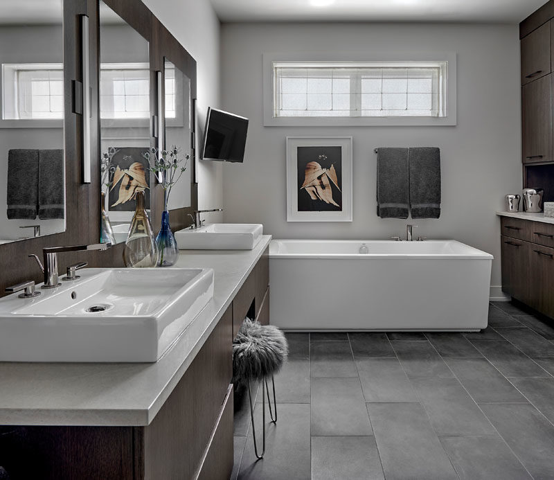 Bathroom Ideas - In this master bathroom, a custom wall hung vanity and back panel has been made from rift cut white oak with an espresso stain, while an engineered quartz counter is complemented by faucets with a titanium finish, and gray porcelain tiles cover the floor. #ModernBathroom #BathroomIdeas #DarkWoodVanity #MasterBathroom