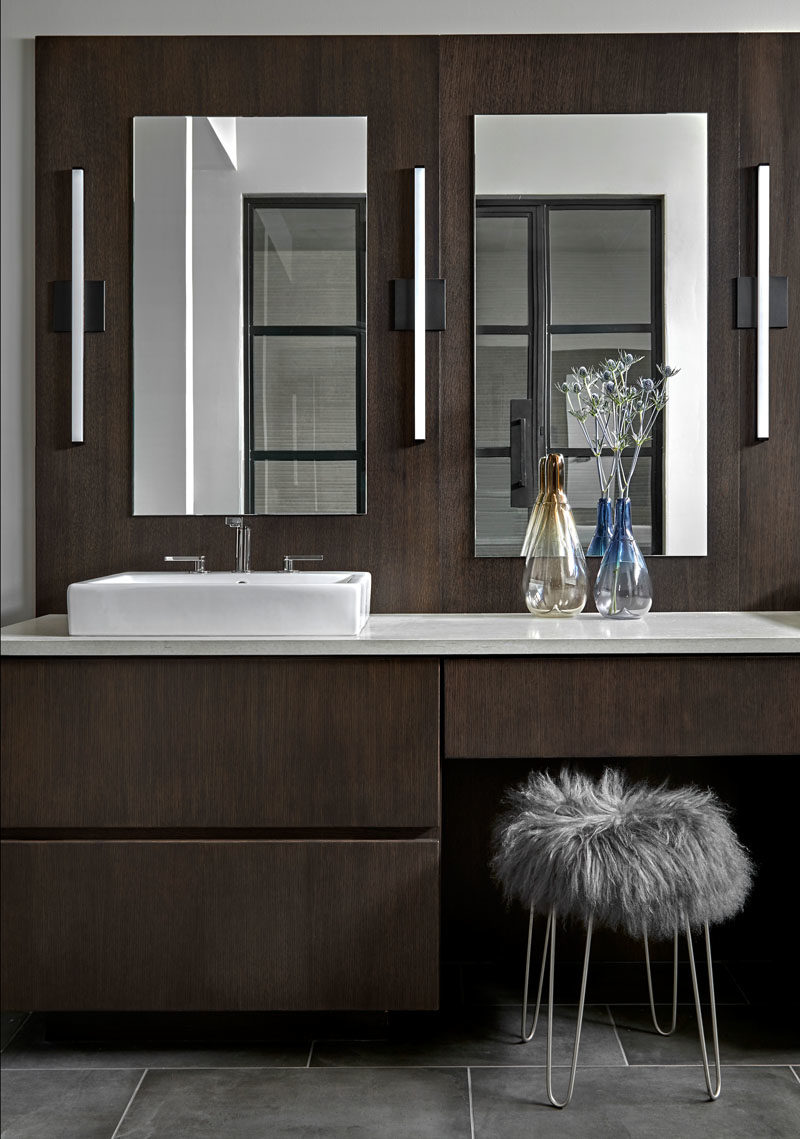 Bathroom Ideas - This modern bathroom features a wall hung  vanity and back panel that's made from rift cut white oak with an espresso stain. Matching back panel. An engineered quartz counter is complemented by Kohler Compose faucets with a titanium finish, while gray porcelain tiles cover the floor. #BathroomIdeas #ModernBathroom #DarkWoodVanity #MasterBathroom