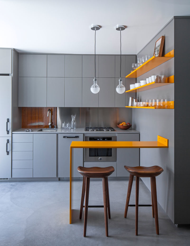 Kitchen Ideas - Stepping inside this modern micro apartment, and the kitchen cabinetry, countertops, and concrete floor exactly match in color, achieved with an integral additive color for the concrete. #GreyAndYellow #SmallKitchen #KitchenDesign #KitchenIdeas