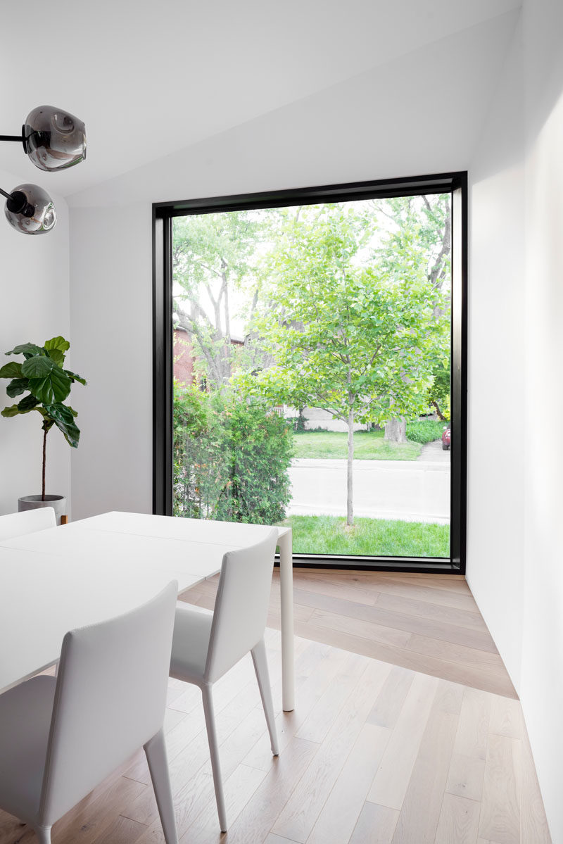 This modern dining room is furnished with a white dining table surrounded by white chairs, while a large picture window frames the street view. #DiningRoomIdeas #WindowIdeas #ModernDiningRoom #BlackFramedWindow