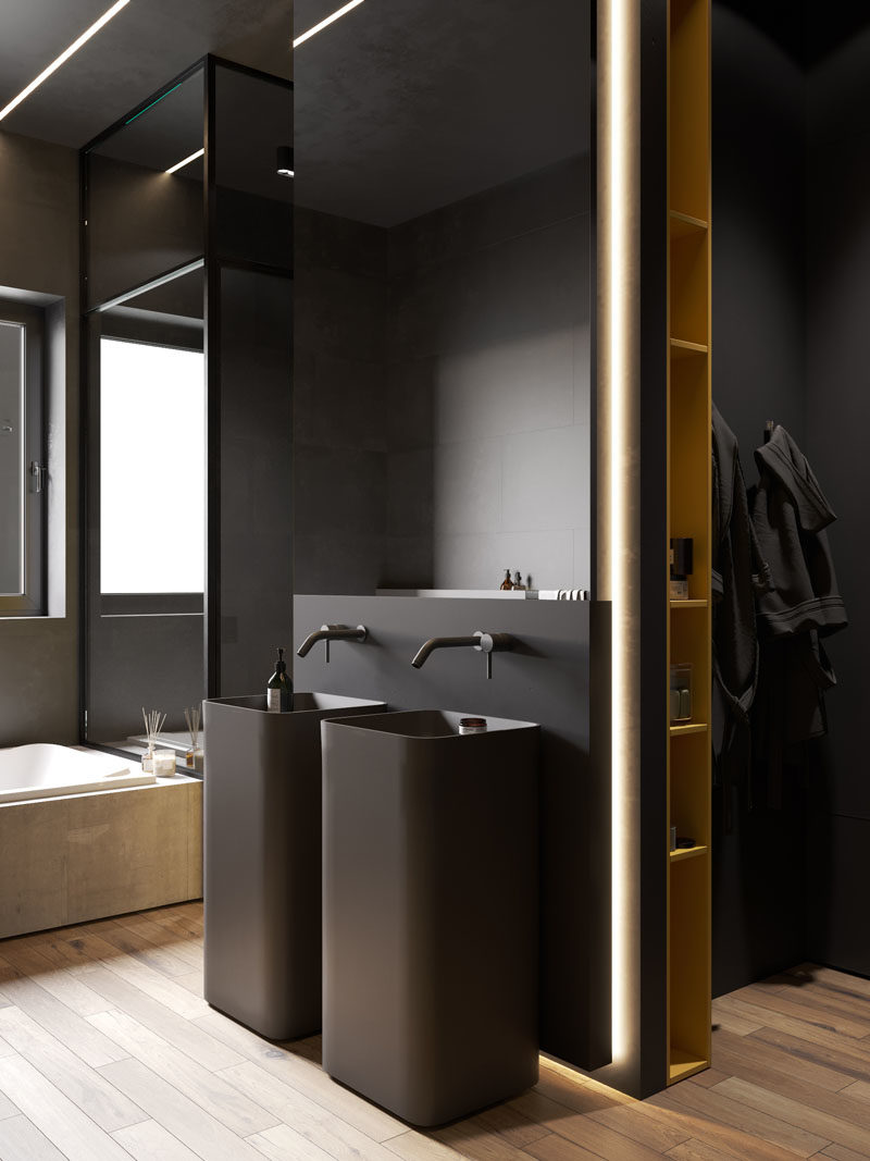 Bathroom Ideas - In this modern bathroom, two black pedestal sinks are located below a mirror, the white bath is built-in and contrasts the rest of the room, and the shower is enclosed by glass and has a built-in shelf with lighting. #BathroomIdeas #ModernBathroom #BahroomDesign #DarkBathroom