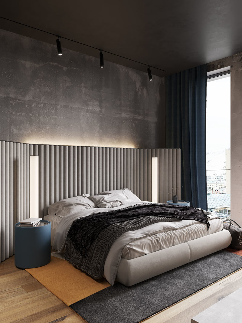Bedroom Ideas - In this modern bedroom, the concrete walls were left bare, while hidden lighting behind the headboard adds a soft glow to the room. #BedroomIdeas #ModernBedroom #BacklitHeadboard