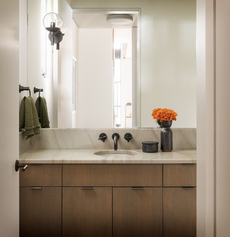 Bathroom Ideas - This modern bathroom features a wood vanity topped with a stone countertop, while a mirror takes up the rest of the wall. #BathroomIdeas #BathroomDesign