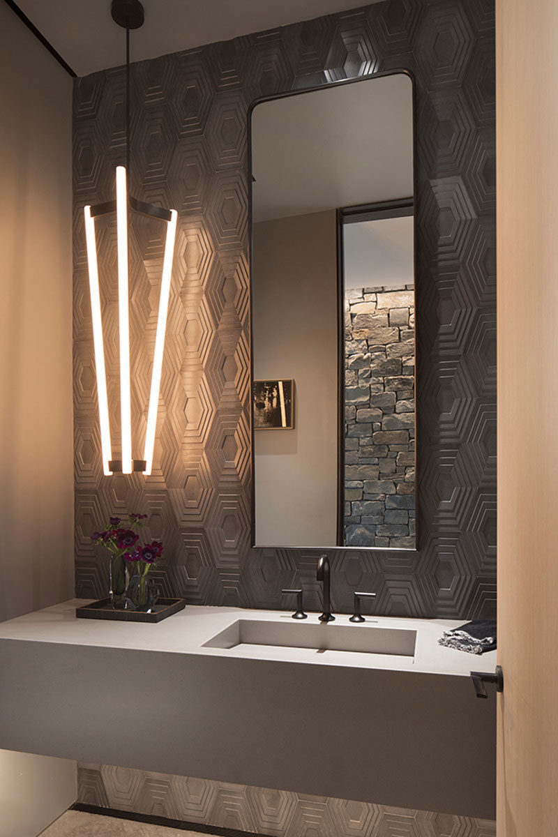 Bathroom Ideas - In this modern bathroom, grey geometric tiles cover the walls, while the tall mirror and long pendant light draw attention to the height of the room. #BathroomIdeas #ModernBathroom