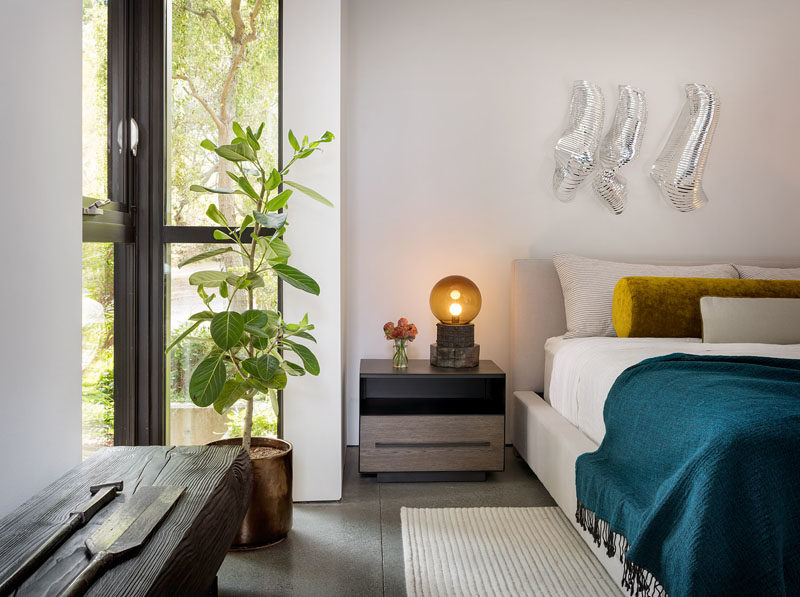 Bedroom Ideas - This modern bedroom features floor-to-ceiling windows in a corner, and a pop of color on the bed in the form of a bolster pillow and a blue throw. #BedroomIdeas #ModernBedroom #BedroomDesign