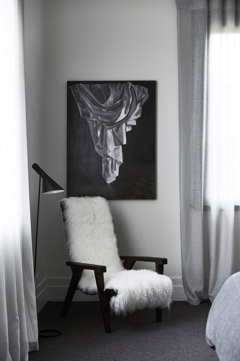 Decor Ideas - In this modern bedroom, a sheepskin is hung over an armchair providing a comfy place to relax, while wall art adds to the black, white and grey color palette. #ModernDecor #DecorIdeas #BedroomDecor