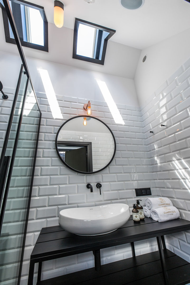Bathroom Ideas - Black design elements are featured in this modern bathroom, with a black vanity, black flooring, and black shower frame. White tiles and skylights help to keep the room bright. #BlackBathroom #BathroomIdeas #Bathroom #ModernBathroom