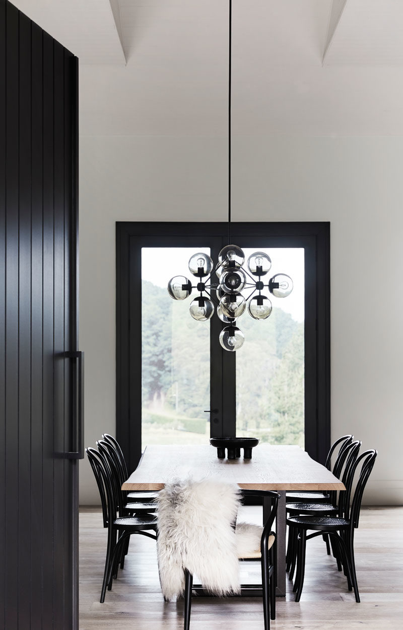 Dining Room Ideas - In this modern farmhouse, a large wood dining table surrounded by black chairs, is positioned beneath a sculptural chandelier. #DiningRoomIdeas #ModernDiningRoom