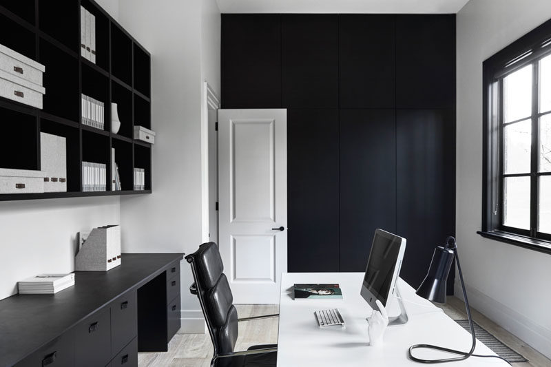 Home Office Ideas - In this modern home office, a black accent wall complements the black shelving and window frames. #ModernHomeOffice #HomeOfficeIdeas #BlackAccentWall
