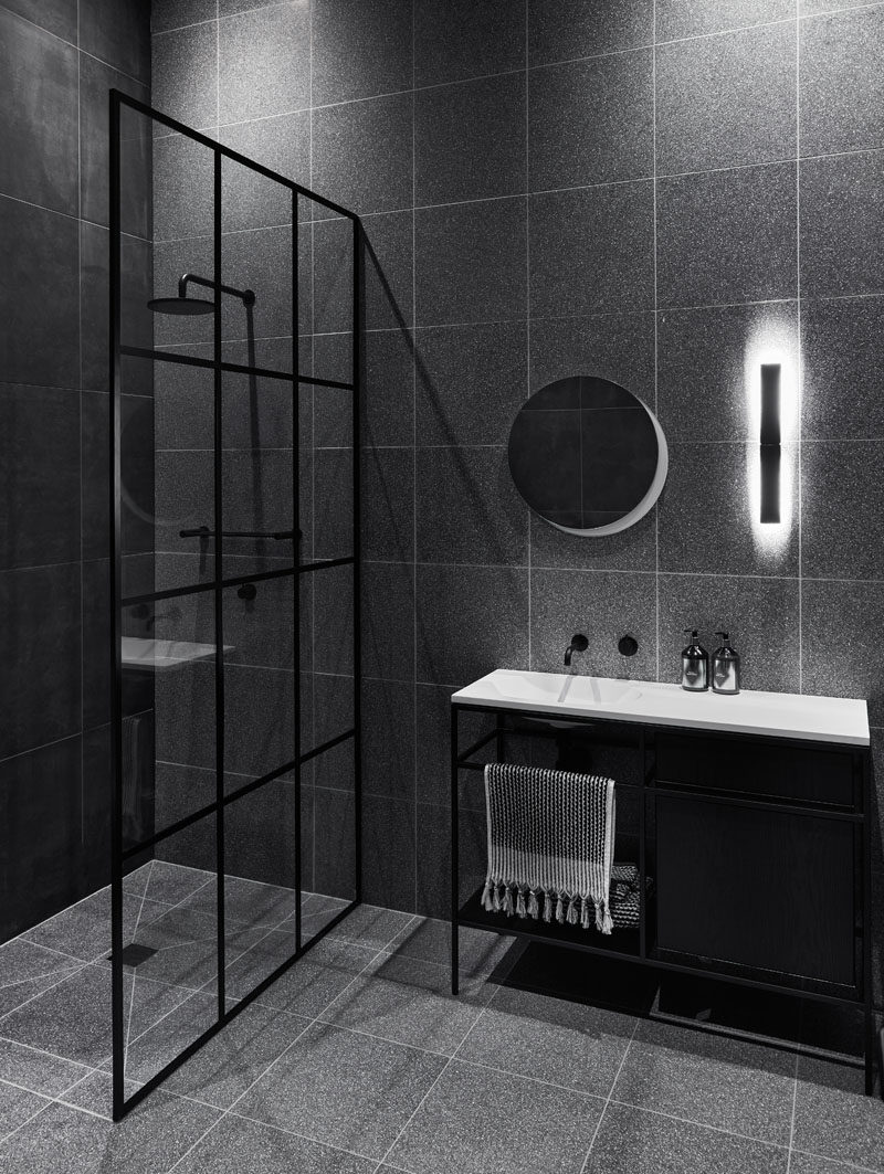 Bathroom Ideas - In this modern black and grey bathroom, a black-frame grid shower screen is inspired by the existing window frames of the house. #BathroomIdeas #BlackBathroom #BathroomDesign