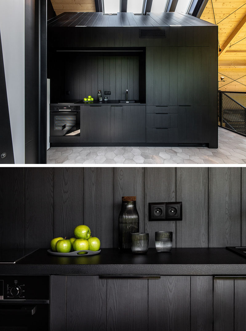 Kitchen Ideas - In this modern black kitchen, black cabinets complement the black dining furniture, the black structural elements, and the black window frames. #BlackKitchen #KitchenIdeas #ModernKitchen #KitchenDesign