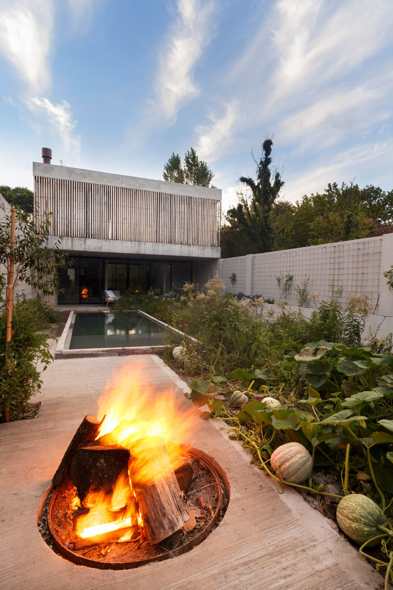 Landscaping Ideas - This modern house has a swimming pool, a vegetable garden, and a patio with a fire pit. #ModernYard #SwimmingPool #Landscaping #LandscapeDesign