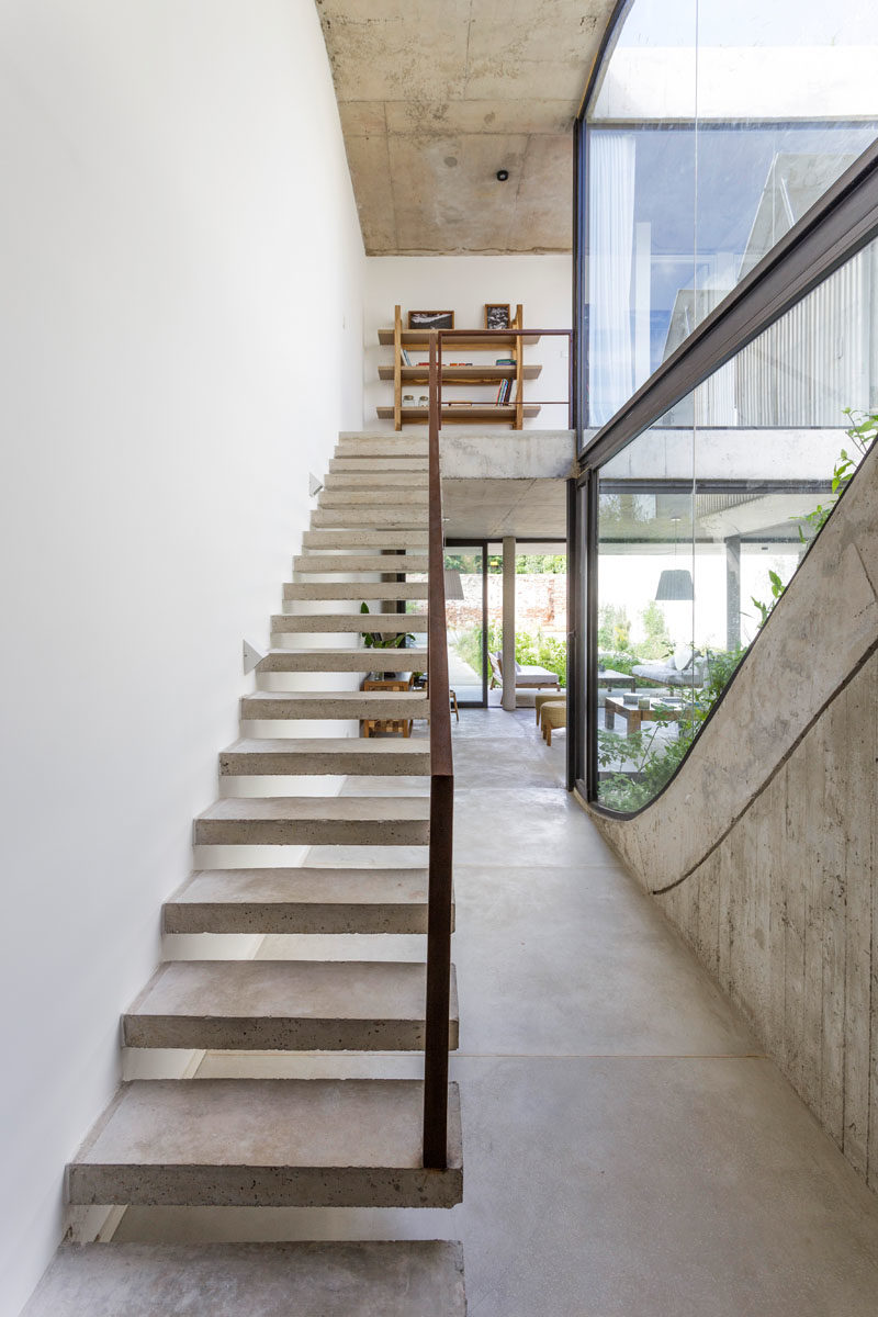 Stair Ideas - Concrete stairs with a steel handrail lead to the upper level of this modern house, where the bedrooms and bathrooms are located. #ConcreteStairs #StairIdeas #ModernStairs