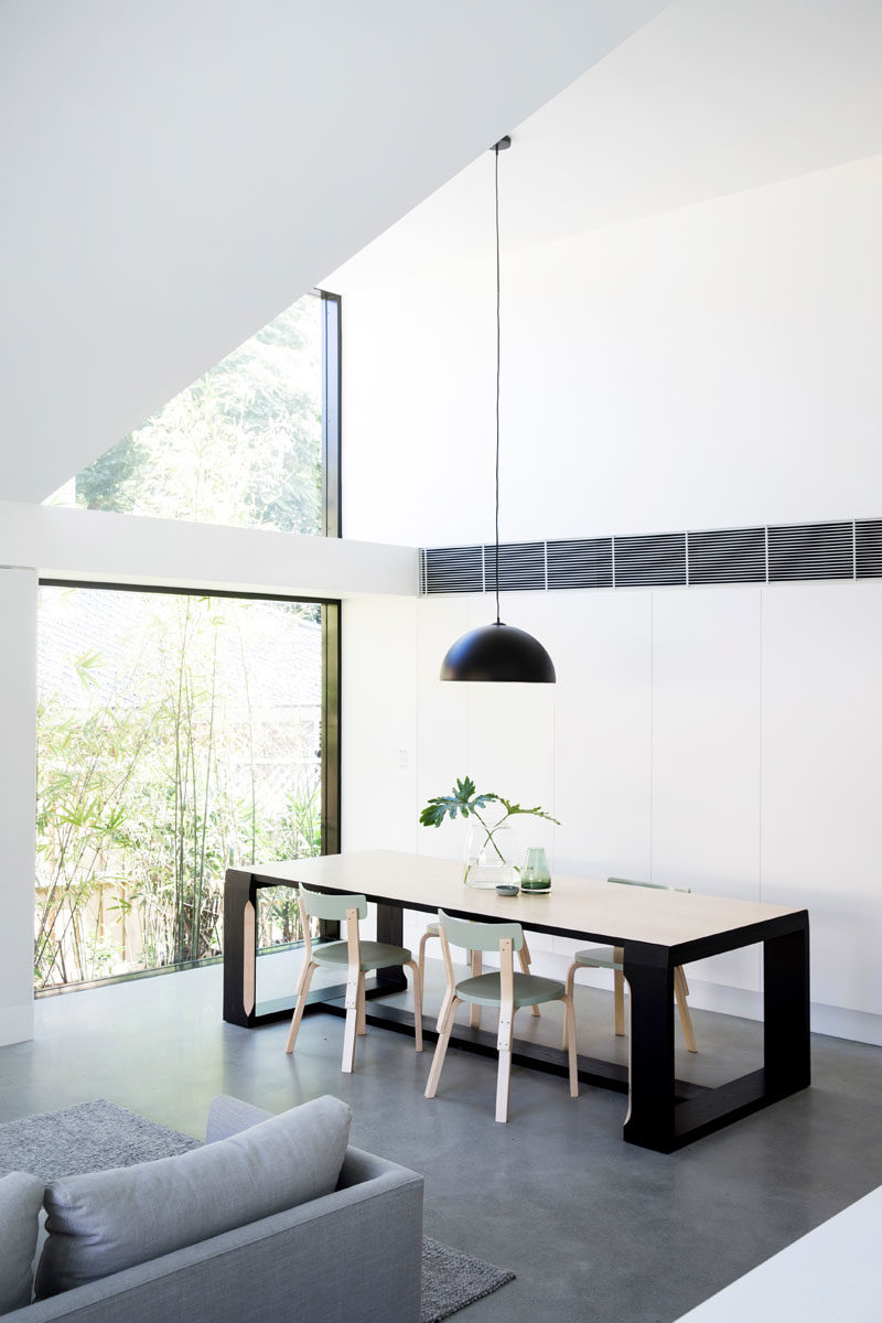 Dining Room Ideas - This modern dining room is positioned next to two large picture windows that frame the trees and let an abundance of natural light into the home. #DiningRoom #Windows #ModernInterior