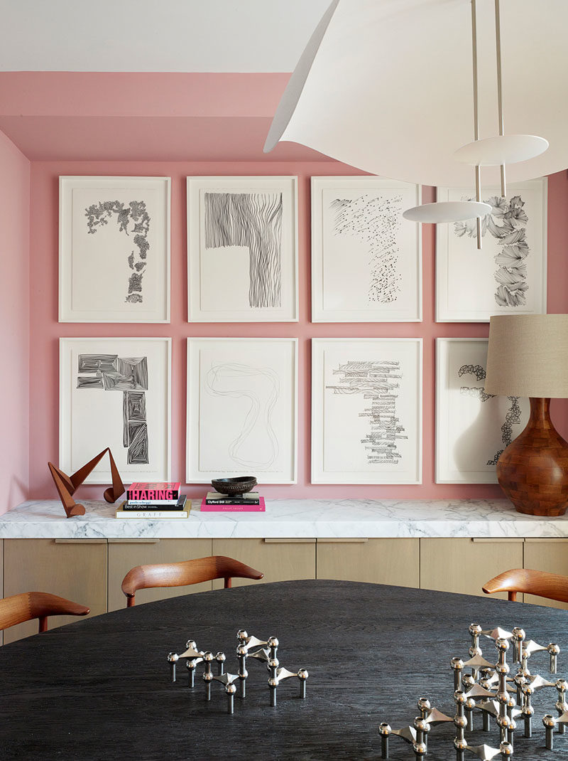 Dining Room Ideas - In this modern dining room, soft pink has been used to create a colorful backdrop for the artwork and dining table, which was designed by Jamie Bush + Co., and is shaped like an oblong pebble with a highly textured wire-brushed finish, that exposes the grain of the blackened oak. #DiningRoomIdeas #DiningRoom #PinkRoom #PinkWalls #InteriorDesign