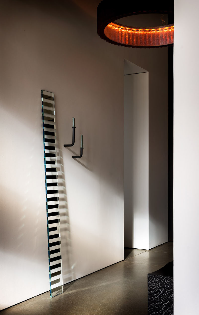 """Hallway Ideas - In this modern hallway, featured pieces are on show, like John Eric Byers' iconic block bench in blackened maple, and a """"Seeing Glass"""" art mirror piece by Sabine Marcelis. #HallwayIdeas #ModernHallway"""