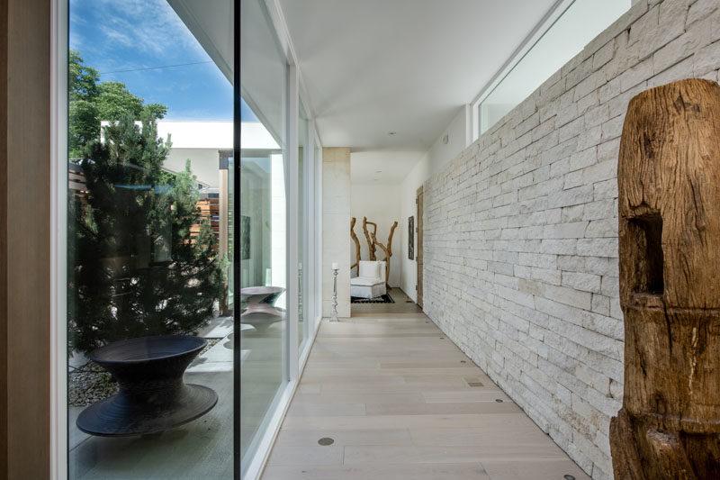 This modern hallway features a floor to ceiling glass wall and a wall of limestone. #HallwayIdeas #HallwayDesign #Windows #LimestoneWall