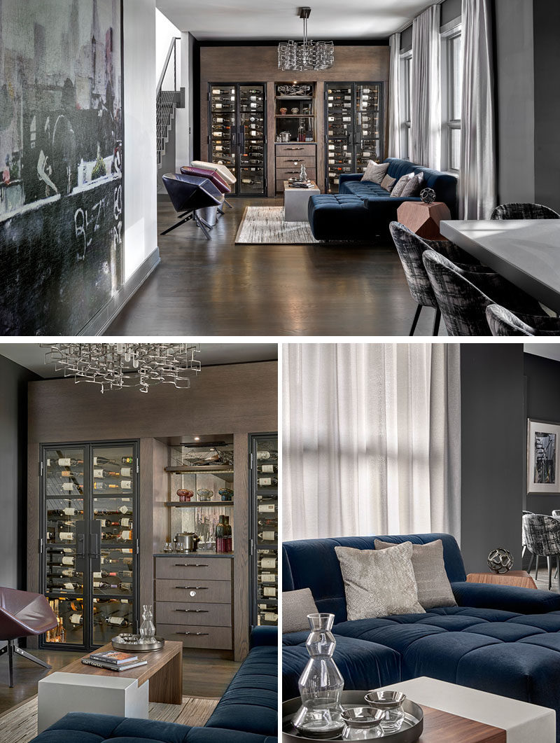 Wine Room Ideas - This modern wine room has been furnished with a ink blue sectional, has custom-built wine chillers, and a chandelier by Lucy Slivinsky, that's made of metal car parts. #WineRoom #WineStorage #Lounge #HomeBar