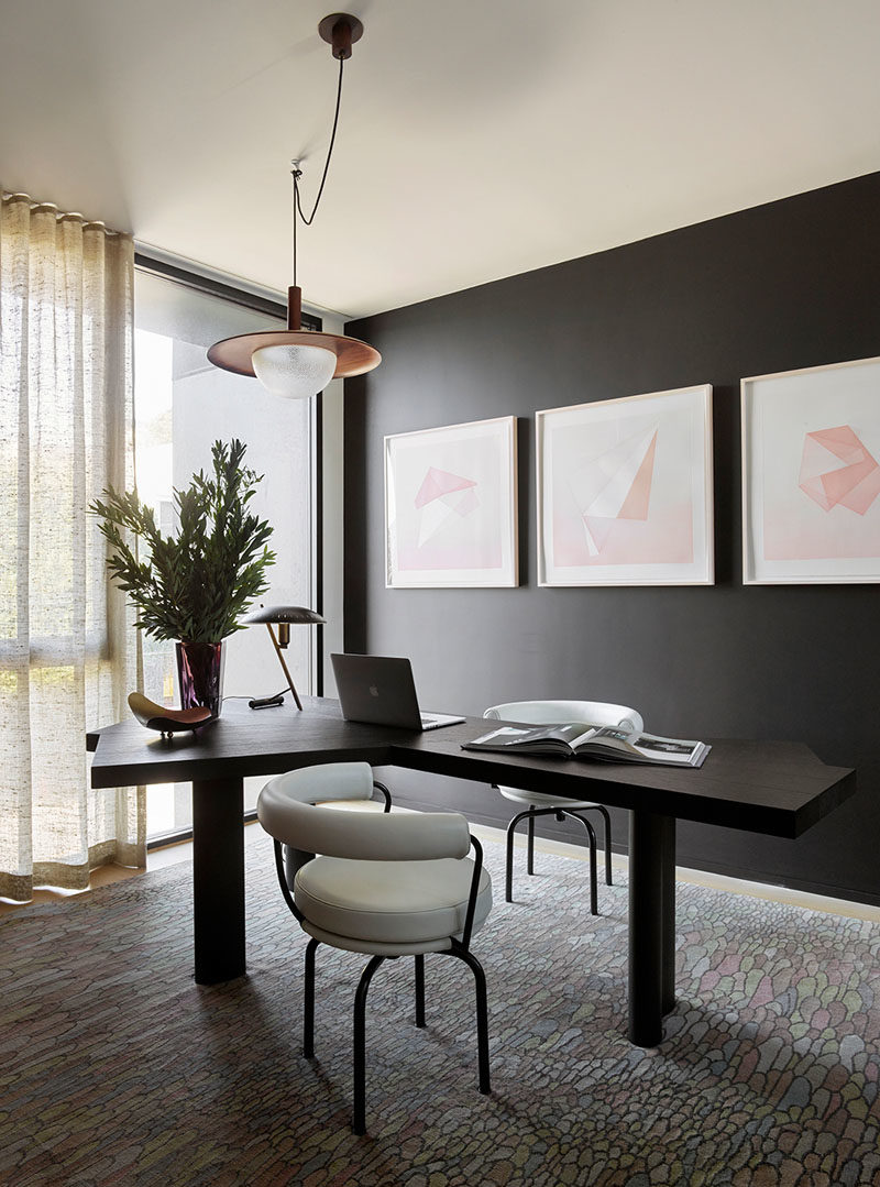 Home Office Ideas - This modern home office has a black accent wall that complements the desk, while light colored artwork and floor-to-ceiling windows helps to keep the room bright. #HomeOfficeIdeas #BlackWall #InteriorDesign