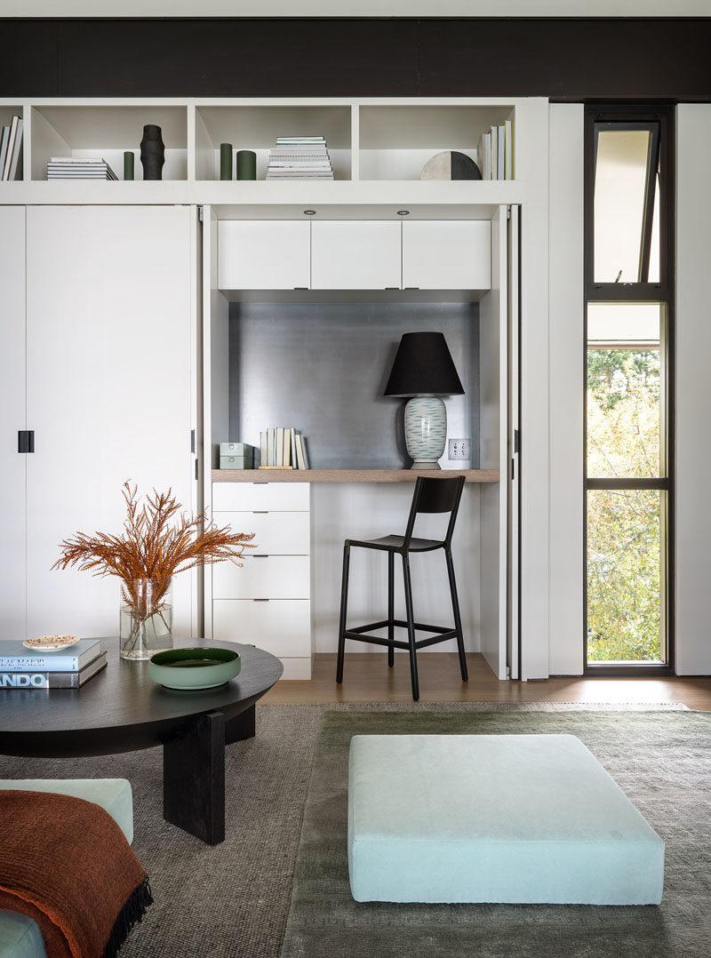 Living Room Ideas - This small living room has a custom-designed shelving unit with a desk hidden within a closet. #HiddenDesk #DeskInCloset #LivingRoomIdeas