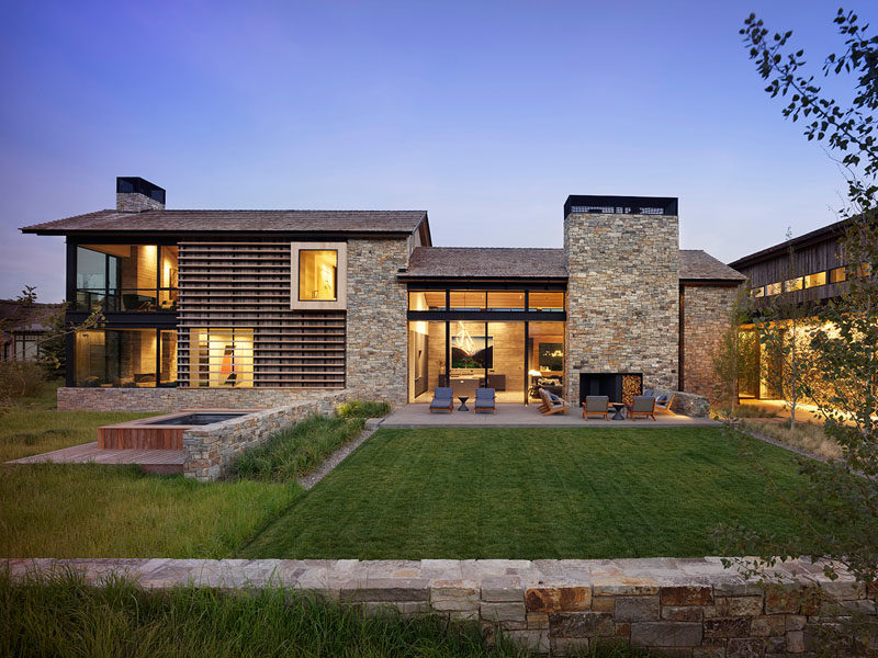 The modern house has a cedar shingle, gabled roof with eaves that extend to protect the reclaimed barn wood siding from the elements. A ribbon of rustic local fieldstone runs the perimeter of the project's base and also clads the chimneys and feature walls. #ModernHouse #HouseDesign #ModernArchitecture
