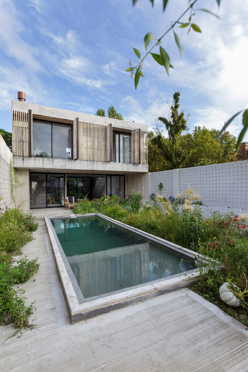 This modern house has a the furnished patio that leads to a swimming pool, as well as modern wood shutters that add a natural touch to the concrete construction of the home. #ModernShutters #ModernHouse #ConcreteHouse #SwimmingPool #Landscaping