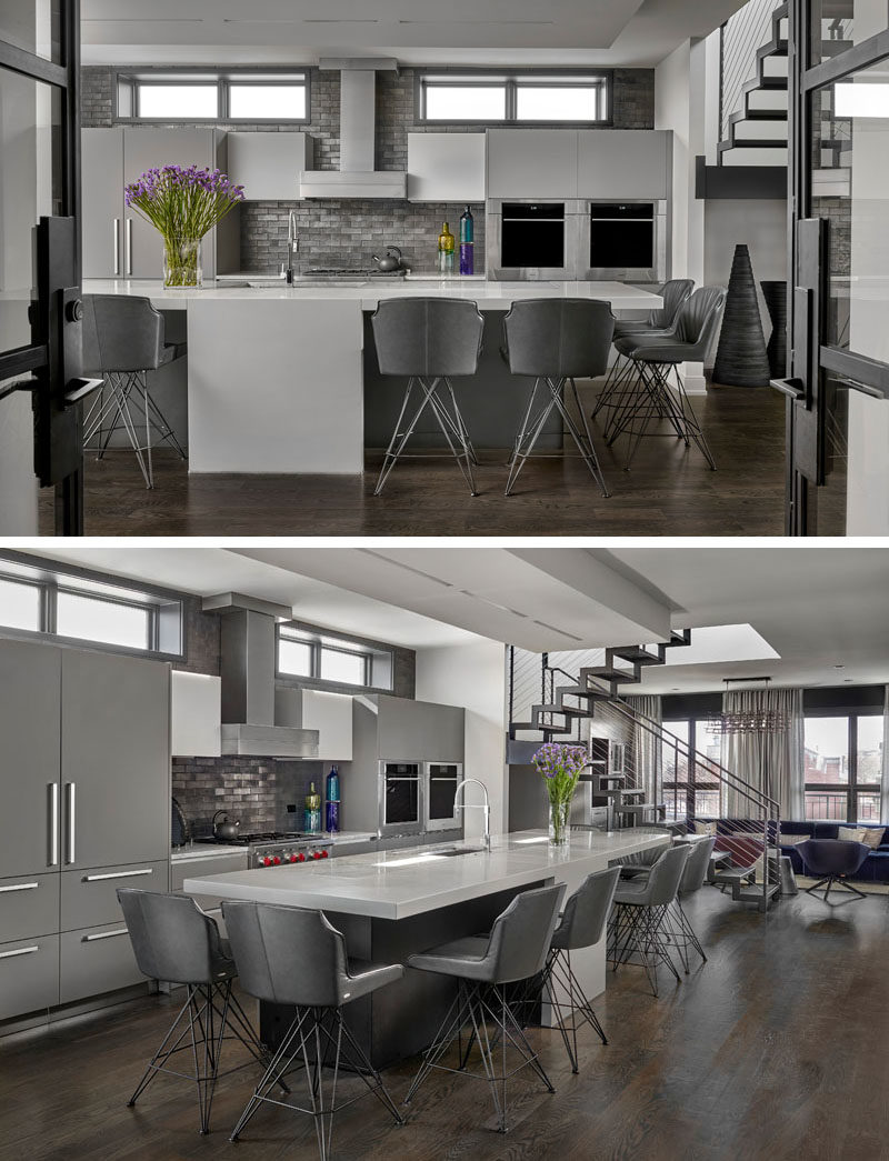 Kitchen Ideas - In this modern kitchen, a double sided 13 foot long, concrete and quartzite island with center waterfall features two eating areas, while the kitchen backsplash showcases exposed brick that's been glazed with gunmetal metallic paint. #KitchenIdeas #ModernKitchen #KitchenIsland #KitchenDesign
