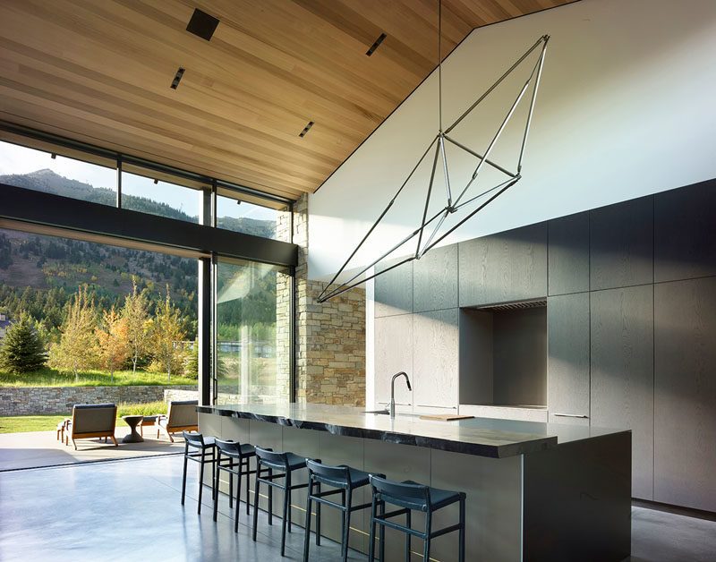 Kitchen Ideas - In this modern kitchen, minimalist dark cabinets and a large island contrast the wood ceiling and white walls. #KitchenIdeas #ModernKitchen #MinimalistKitchen