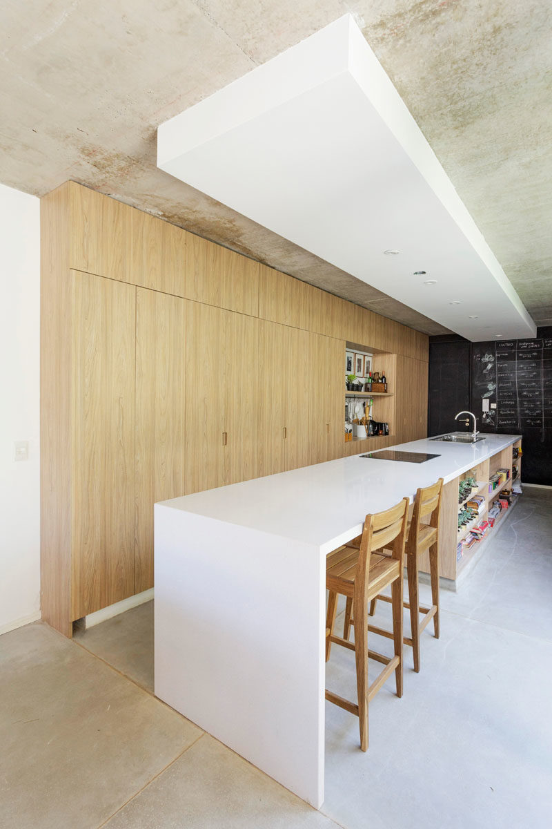 Kitchen Ideas - In this modern kitchen, floor-to-ceiling light wood cabinets have been combined with a long white island for a minimalist look. #ModernKitchen #KitchenIdeas #KitchenDesign