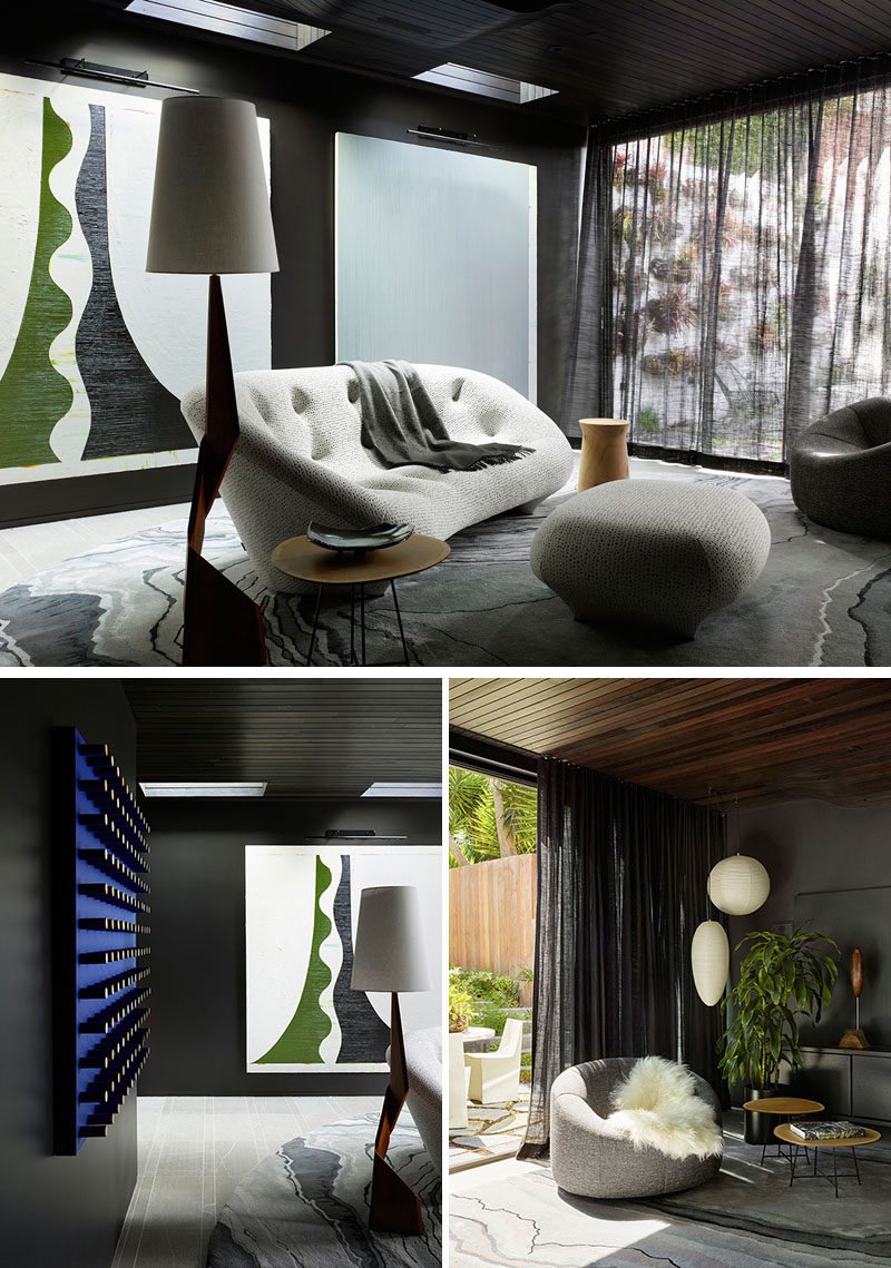 Living Room Ideas - This dark lounge has bold artwork and a vintage Danish sculptural floor lamp from the 1960's. #LivingRoomIdeas #BlackWalls #LivingRoom