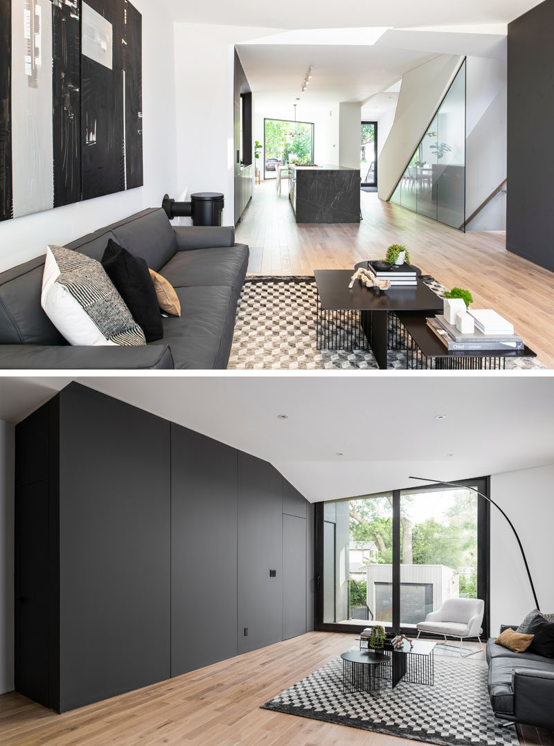 Living Room Ideas - A minimalist black accent wall matches the kitchen and hides a powder room and mudroom. #ModernLivingRoom #LivingRoomIdeas #BlackAccentWall #BlackFeatureWall