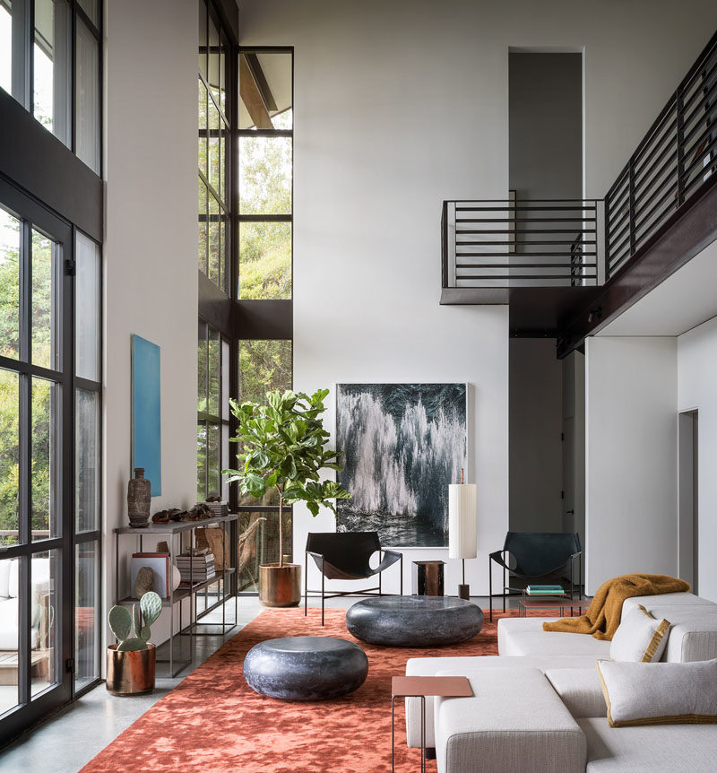 Living Room Ideas - Double height windows in this modern living room frame the picturesque bay and illuminate the silk Tai Ping rust carpet, while the Laurier Blanc acrylic glass Hekla Side Table & Stool, complement the Taylor Forest club chair, that sits beneath the Amir Zaki waterfall photograph. #LivingRoomIdeas #InteriorDesign #LivingRoom #ModernInterior