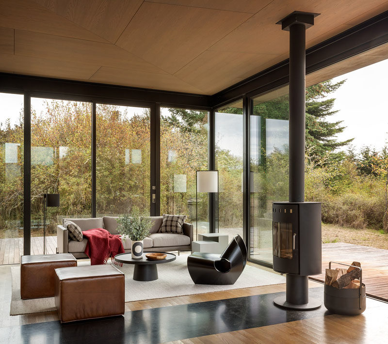 This modern guest cabin is furnished with Made in Ratio's sculptural Cowrie Chair, a TRNK Truss Sofa and sculptural side table, and the Rodan Coffee Table by Pinch. #InteriorDesign #GlassWalls #CabinDesign