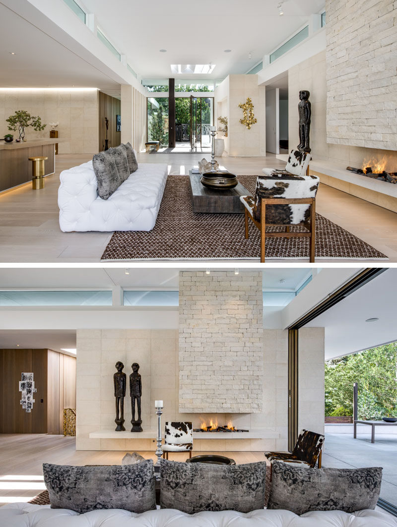Living Room Ideas - The front entryway of this modern house opens up to the living room that showcases limestone walls and an open flame fireplace. #LivingRoom #Fireplace #LimestoneWalls