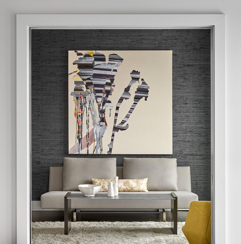 This small lounge area is highlighted by the dark grey accent wall, the large art piece, and a colorful yellow armchair. #InteriorDesign #ModernInterior