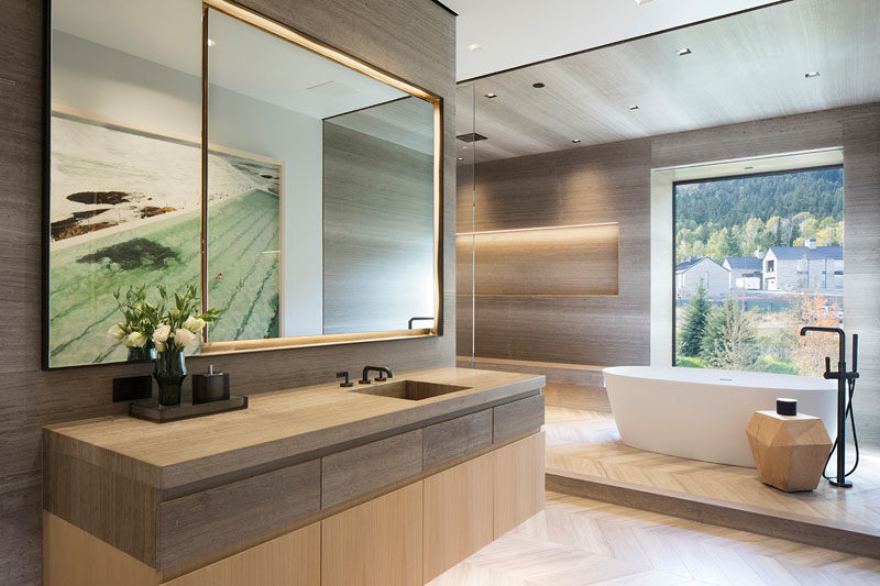 Bathroom Ideas - In this modern master bathroom, hidden lighting creates a soft glow, while the freestanding bathtub has been raised up on a platform and positioned beneath the window. #BathroomIdeas #ModernBathroom #MasterBathroom