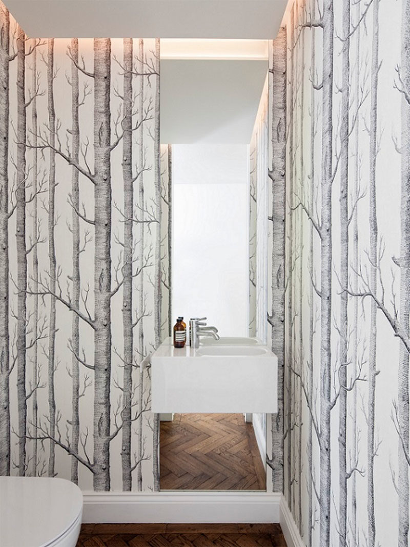 Bathroom Ideas - In this modern powder room, nature has been brought inside with the use of wallpaper with trees. #Bathroom #PowderRoomIdeas #Wallpaper