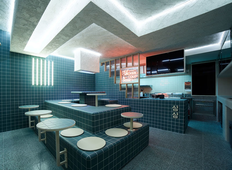 Restaurant Ideas - Deep blue-green tiles and tiered seating have been used throughout this modern restaurant to create a unified appearance that's inspired by retro 60's style and Korean bath houses. #Tile #RestaurantDesign #RestauarantIdeas