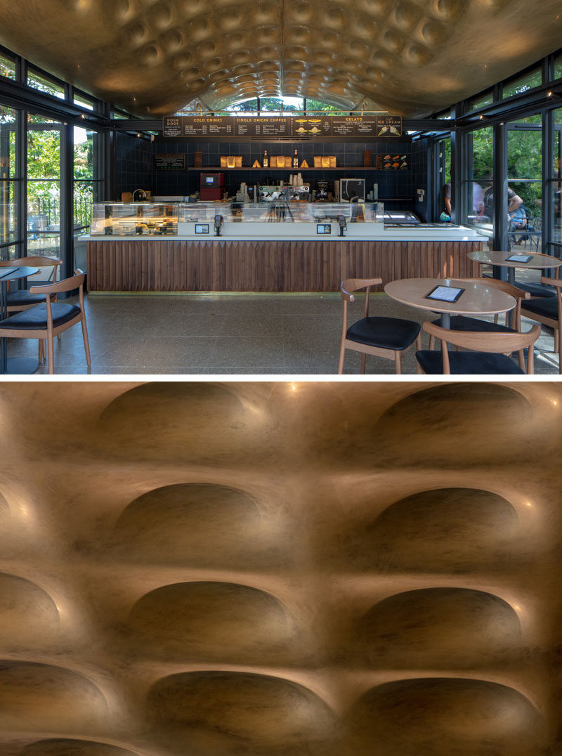 The undulating canopy of this modern coffee house, designed to respond to the movement of the nearby lake, has been hand-painted using specialist techniques to give an aged-brass finish, and is intricately textured on the underside with snakeskin-inspired, coffer-like dimples. #Ceiling #AccentCeiling #Architecture #ModernArchitecture #Design