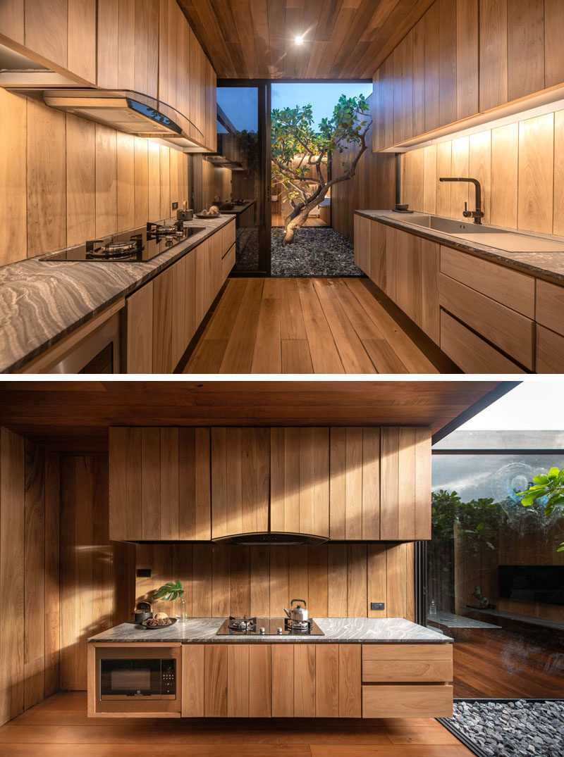 Kitchen Ideas - This modern kitchen has floating wood cabinets and access to a small courtyard with a tree. #ModernWoodKitchen #KitchenIdeas #WoodCabinets