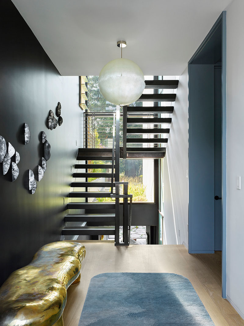 Inside this modern house, there's a clear view from the foyer of the rear garden and the stairs that connect the various levels of the home. #InteriorDesign #Stairs #StairIdeas