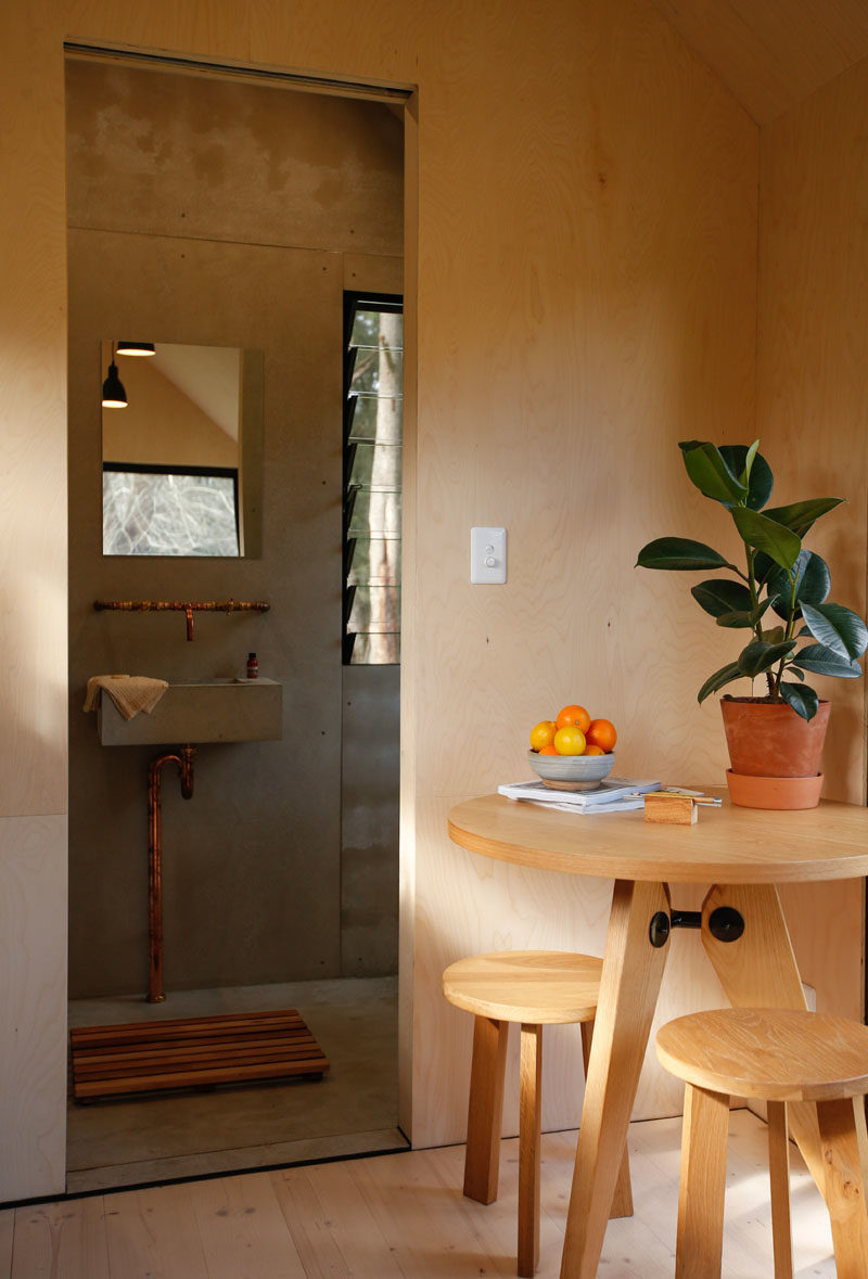 A sliding door in this tiny house opens to reveal the bathroom, where there's a composting toilet, vanity area, and a shower. #TinyHouse #TinyHome #Bathroom