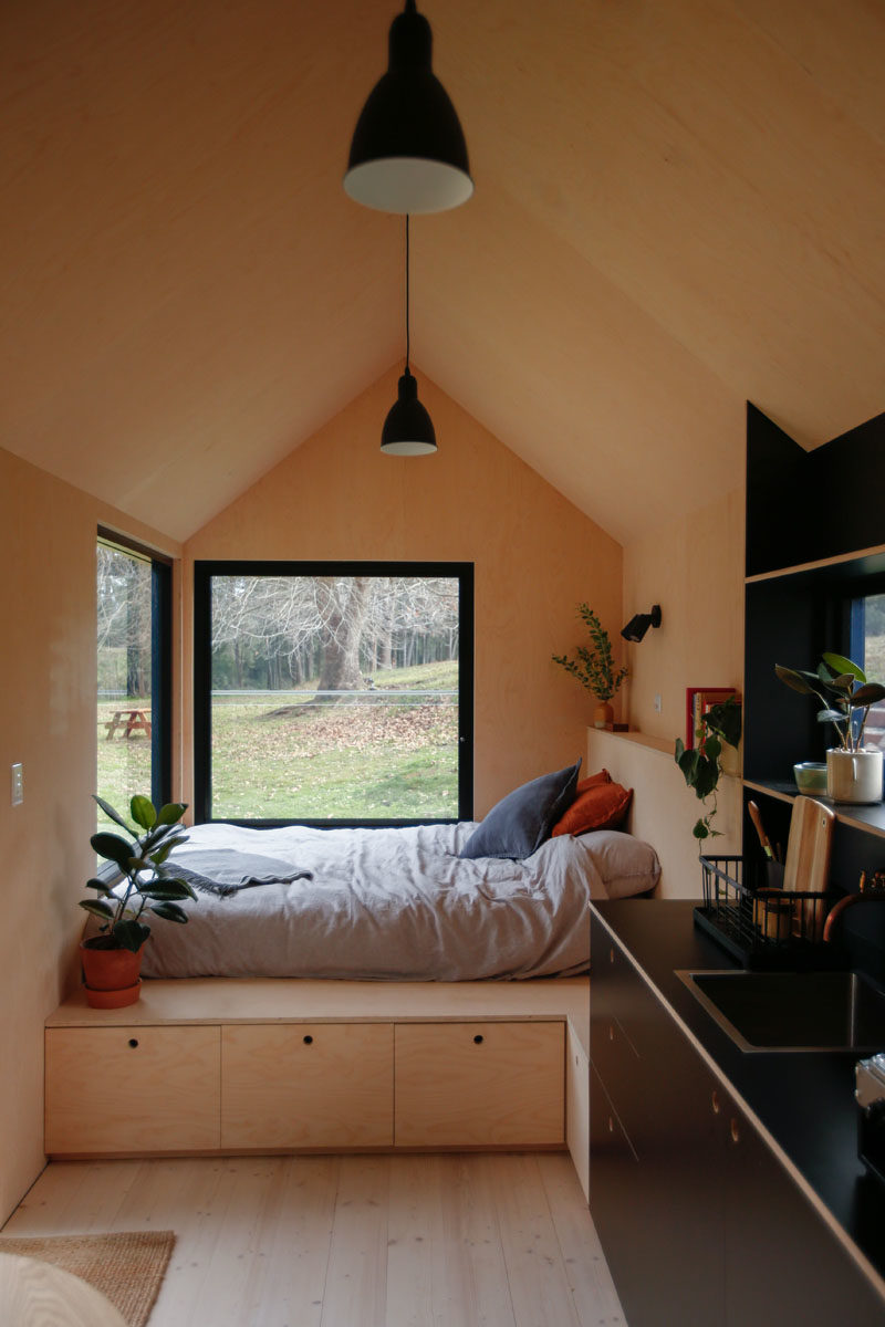At one end of this modern tiny cabin is the open bedroom, that has two large windows, providing natural light and views of the trees outside. Storage has been added underneath the bed, and also acts as a bench to sit on. #TinyCabin #TinyHouse #TinyHome #Bedroom #Windows