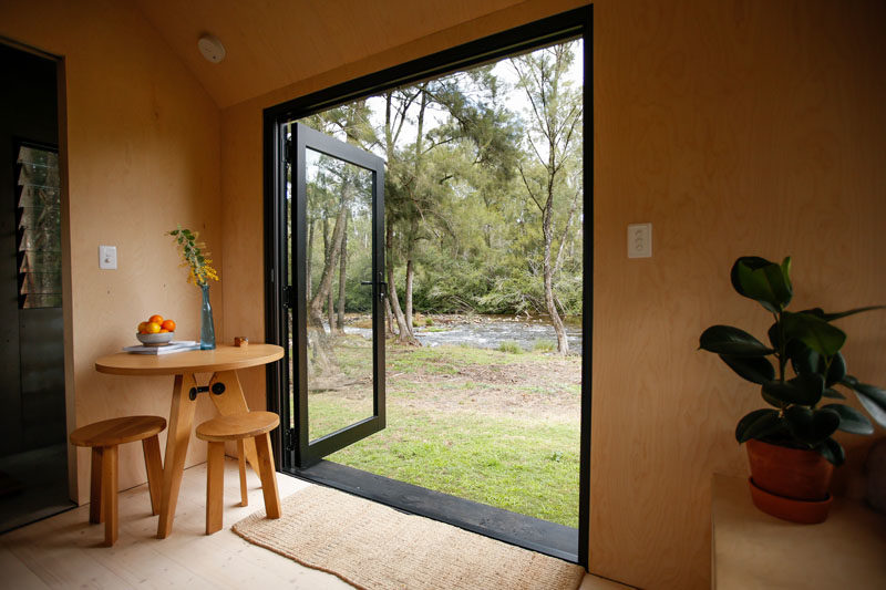 The black-framed glass french doors of this tiny house can be opened to help make the interior feel larger. Just inside the doors is a small corner dedicated to a round table and a pair of stools. #TinyHouse #TinyHome #TinyCabin #Doors