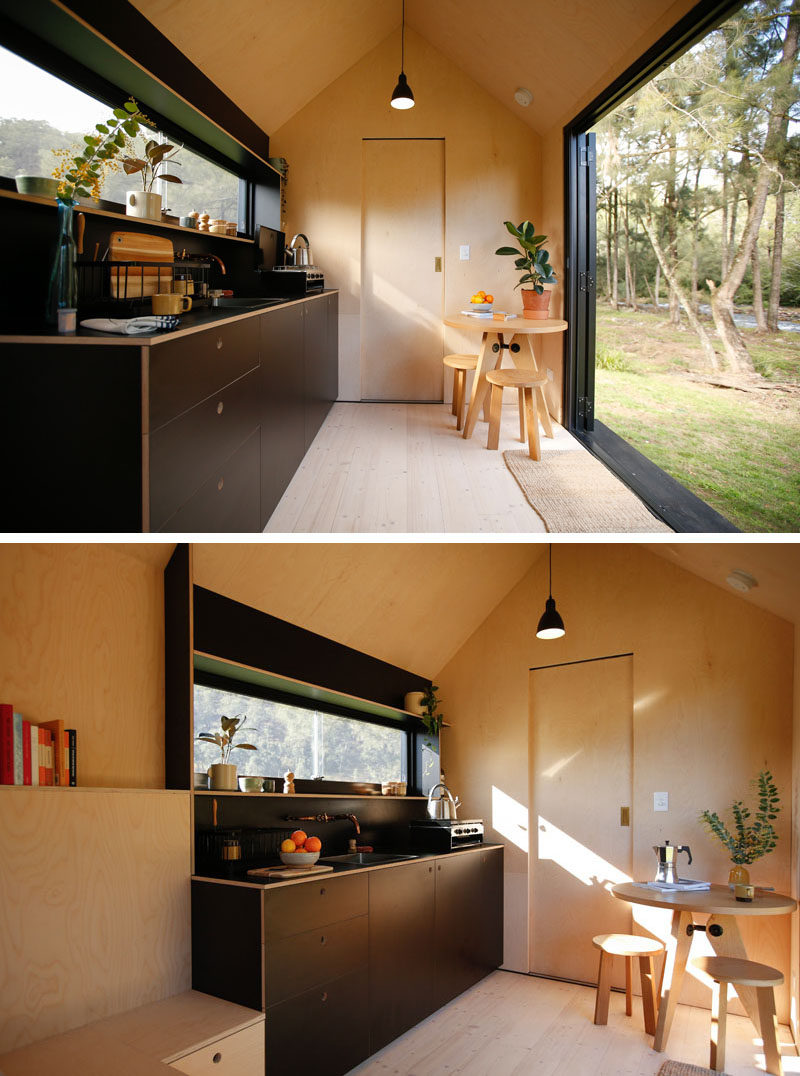 This modern tiny cabin has a cathedral ceiling adding to the sense of openness, while the dark kitchen cabinets and shelving are located around a long horizontal window. #TinyHouse #TinyHome #TinyCabin #BlackKitchen